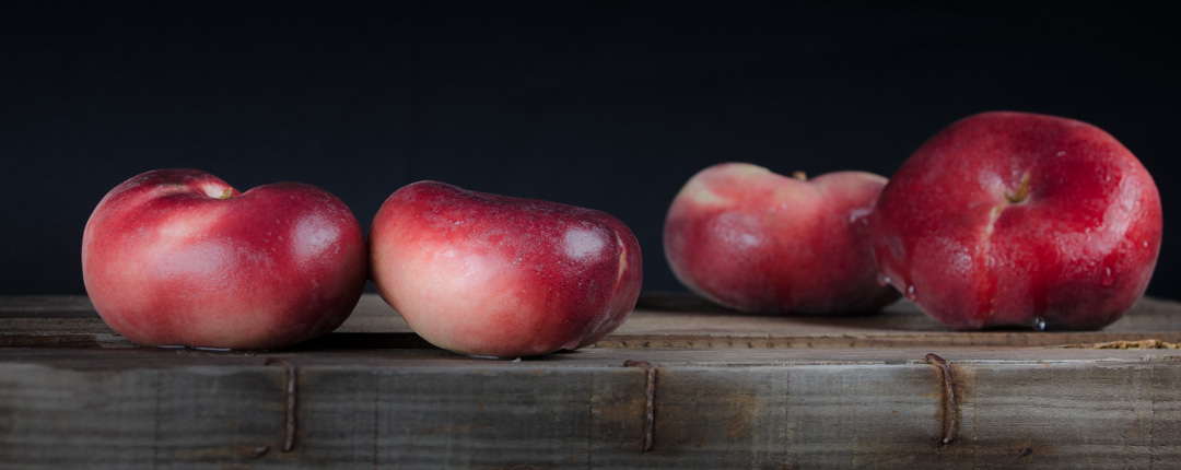Doughnut peaches are recognisable for their flattened shape and smooth, shiny, hairless skin